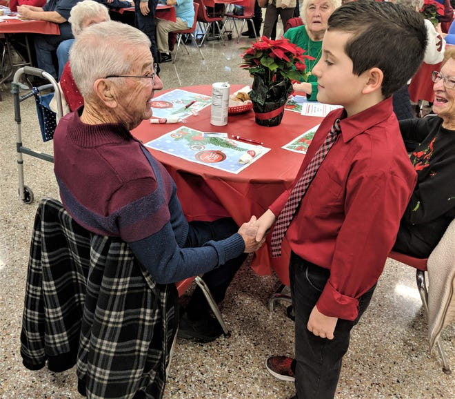 Richard Stein is greeted by Trevor Mares at the PCHS Holiday Breakfast with the Arts.  David Stover and his grade 2 Humble and Kind members helped welcome guests to the breakfast.