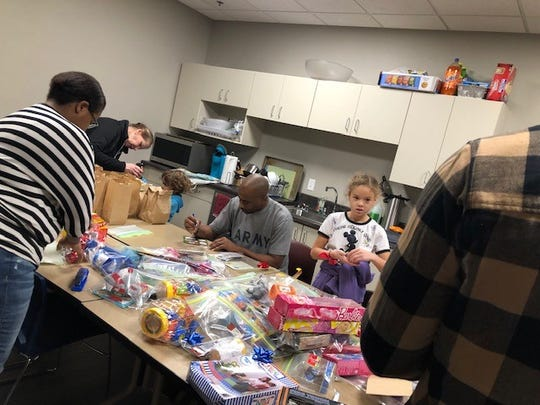Volunteers from Young Life Green Bay prepare gifts Sunday for people who will attend Wednesday's free community Christmas dinner at Spring Lake Church on North Adams Street.