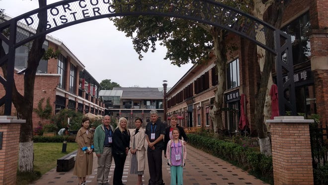 County board members and Jingdezhen market square management under a sign leading to the square that recongizes Door County as its Sister City.
