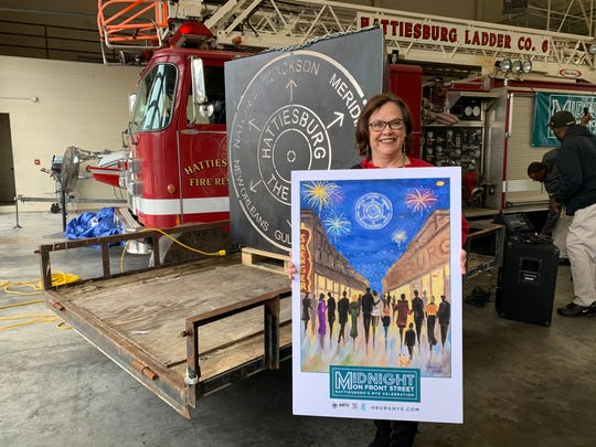 Glenda Grubbs shows a poster of her painting showing downtown Hattiesburg. The poster will be used by the city of Hattiesburg for its Midnight on Front Street New Year's Eve celebration.
