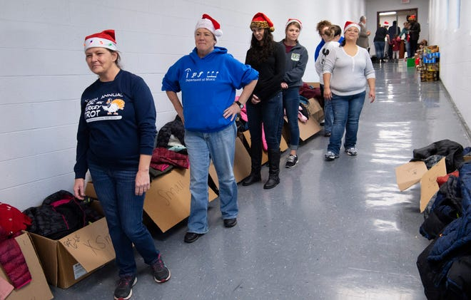 Volunteers stand at-the-ready to fit the 4-11-year-old youngsters with winter coats at the Goodfellows Christmas Party at South Middle School Sunday afternoon, Dec. 22, 2019.