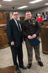 Henderson County Sheriff's Deputy Aaron Daniels (right) poses with County Judge-executive Brad Schneider after being honored for heroic actions taken this fall (Dec. 23, 2019).