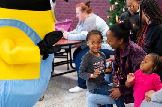 Journee Carter, 3, center, isn't too sure about visiting the Minion at the Goodfellows Christmas Party at South Middle School Sunday afternoon, Dec. 22, 2019. Her mom, Jasmine Hancock and sister, Jazaree Carter, 2, encouraged her to say hello.