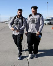 Iowa defensive end A.J. Epenesa, left, and offensive tackle Tristan Wirfs get ready to board the team plane Saturday. The elite juniors are preparing for the Holiday Bowl and will have an NFL decision to finalize soon.