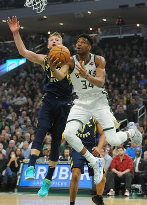 Dec 22, 2019; Milwaukee, Wisconsin, USA;  Milwaukee Bucks forward Giannis Antetokounmpo (34) drives the baseline against Indiana Pacers forward Domantas Sabonis (11) at Fiserv Forum.