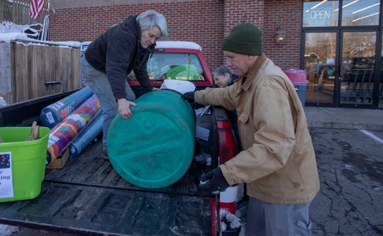 Mary Stumpp (left), works with friends Susan Shepherd and Jim Poyser to load up a can of old holiday lights for the Can Lady Project, a local recycling effort that this time of year, is collecting old lights that will be broken apart for their copper and turned into cash for donation, Indianapolis, Thursday, Dec. 19, 2019.
