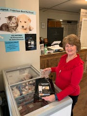 Brenda Smithers, an employee at the Remington-Lott Farms store in Ridgeland, shows how Loyal Legends premium beef pet food is packaged.