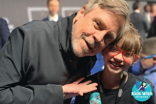 """Actor Mark Hamill enjoys a moment with Addisyn Richards of Gulfport, Miss., at the premiere of """"Star Wars: The Rise of Skywalker."""""""