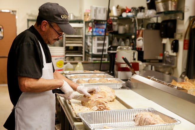 Saul Alvarez cuts turkeys inside the Outpost Catering kitchen, Monday, Dec. 23, 2019 in Lafayette. The turkeys will be served during a community dinner at Lafayette Jeff High School on Christmas day from 11 a.m. to 2 p.m.