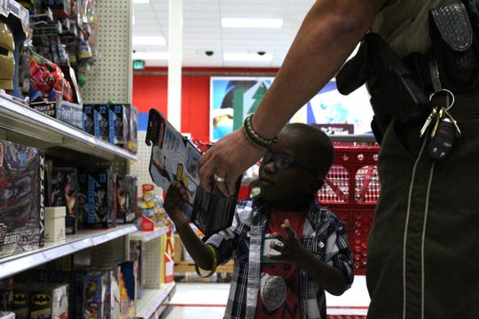 Ronquail Ollison Jr. (R.J.), a 5-year-old pre-K student at Truman Elementary, looks over a Spiderman toy with his school resource officer Cpl. Thomas Babineaux during the Shop with a Cop event on Dec. 23, 2019.
