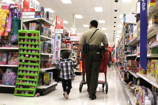 Ronquail Ollison Jr. (R.J.), a 5-year-old pre-K student at Truman Elementary shops with school resource officer Cpl. Thomas Babineaux at Target during the Shop with a Cop event on Dec. 23, 2019.