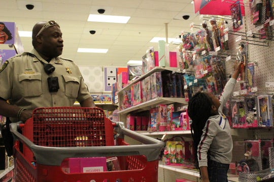 Lafayette Parish Sheriff's Office Cpl. Chris Wright, a student resource officer, helps Ja'Naveya Porter, an 8-year-old second-grader at Evangeline Elementary, pick out Barbie dolls at Target during the Shop with a Cop event on Dec. 23, 2019.