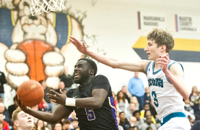 Male guard Tyren Moore tries to score paint North Oldham forward Ian Higdon during the semi-final game of the 39th annual King of the Bluegrass tournament. Dec. 22, 2019