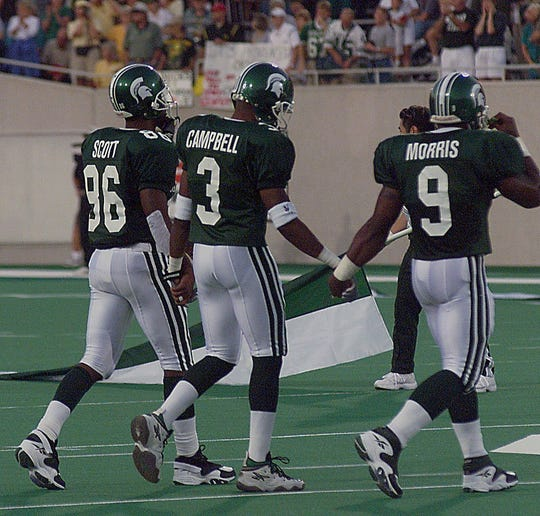 Back from a serious injury, MSU cornerback Amp Campbell, center, goes to the coin toss with teammates Gari Scott, left, and Aric Morris, right, before MSU's season-opener against Oregon on Sept. 2, 1999.