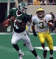 MSU's Plaxico Burress eludes Michigan defender Todd Howard, right, on a 68-yard pass play  in 1999. Burress caught 10 passes in the Spartans' win.