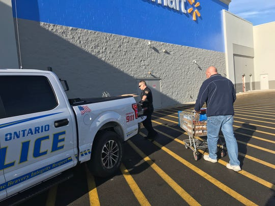 Mike Dallas drops off a cart full of canned goods  outside Walmart in Ontario on Monday to the Cram the Cruiser non-perishable food drive for Richland County food pantries. Ontario police Officer Rod Roose, at left, loaded residents' canned goods and more into the department's F-150 pickup.
