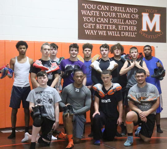 2015 Mansfield Senior grad and current assistant wrestling coach Jesse Palser, (front-right) shown here with the 2019-20 Tygers wrestling team, is on a mission to open a shoe bank allowing Mansfield youngsters who cannot afford wrestling shoes the opportunity to borrow a pair in order to compete.