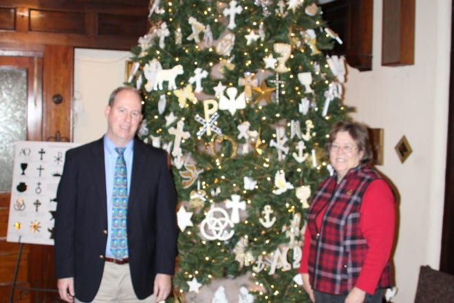 First Presbyterian Church pastor Rev. Rob Howard, left, and church member Barb Arms stand in front of the church's Chrismon tree. The tree is decorated with various symbols of the Christian faith called Chrismons. Arms' mother, Betty Black, started the tradition of decorating a Chrismon tree at First Presbyterian back in 1972.
