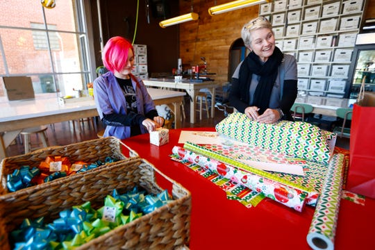 Theresa Rich and her daughter Jane put the finishing touches on their Christmas presents at the wrapping station inside the Five in One Social Club in the Binghampton neighborhood on Monday, Dec. 23, 2019.