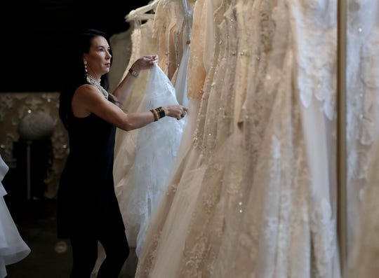 Christina Alexander Wegner straightens bridal gowns at her second store, White Dress Off the Rack.