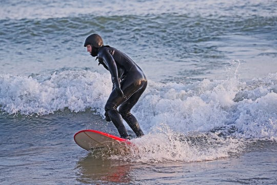 Hart Moss of Milwaukee surfs in Lake Michigan at Bradford Beach over the weekend. The high temperature Sunday equaled a record set in 1875 and the forecast calls for more unseasonably warm weather this week.