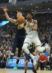 Bucks forward Giannis Antetokounmpo  drives the baseline against Indiana Pacers forward Domantas Sabonis Sunday night.