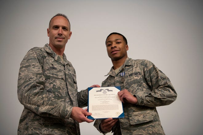 Lt. Col. Scott Corey, 42nd Operational Medical Readiness Squadron commander, presents Airman 1st Class Vashon Williams, 42nd OMRS dental assistant, with the Air Force Achievement Medal during a ceremony December. 19, 2019, at Maxwell Air Force Base, Alabama. Williams witnessed the aftermath of a four-car pileup and performed life-saving first aid to several victims.