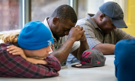 Residents bow their heads and pray before lunch is served at the Salvation Army soup kitchen in Montgomery, Ala., on Tuesday May 7, 2019.
