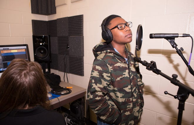 Ball State student Tessa Chason supports a student as he prepares to record rap in the studio.