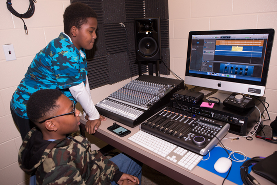 Two middle schoolers work on their recording project in Buley's studio.
