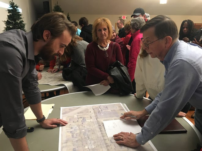 Dave Heilman, one of the designers of the proposed West Riverside Avenue trail, listens to the concerns of a neighbor during a meeting on Dec. 17 at Westminster Presbyterian Church.