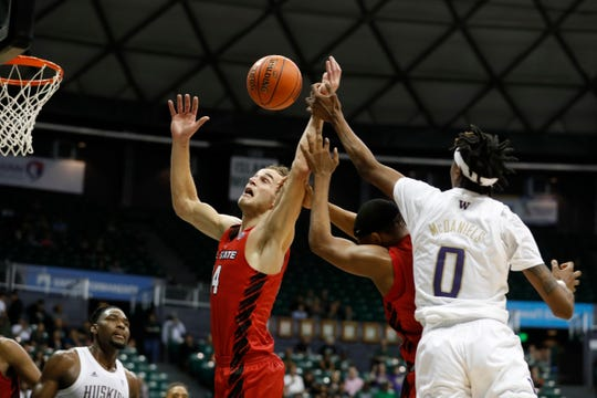 Ball State guard Lucas Kroft (4) and guard Jarron Coleman (11), second from right, fight for a rebound over Washington forward Jayden McDaniels (0) during the second half of an NCAA college basketball game, Sunday, Dec. 22, 2019, in Honolulu. (AP Photo/Marco Garcia)