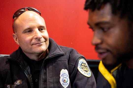 Nashville police officer Steve Fouche looks at Dillard Smith NY Pie Wednesday, Dec. 18, 2019, in Nashville, Tenn. The two often have lunch together and check in.