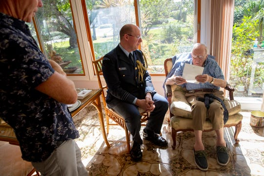 Thomas Horton, right, who served in the Royal New Zealand Air Force in WWII, reads a letter wishing him a happy 100th birthday and thanking him for his service while Wing Commander Graham Streatfield, center, and Horton's son Peter Horton, left, listen at Horton's home in Naples on Monday, Dec. 23, 2019. Horton turns 100 on Dec. 29.
