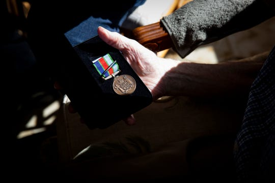 Thomas Horton, who served in the Royal New Zealand Air Force in WWII, receives a Defence Service Medal from Wing Commander Graham Streatfield at Horton's home in Naples on Monday, Dec. 23, 2019.