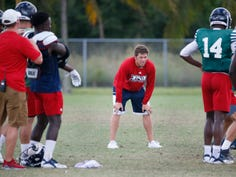In this Tuesday, Aug. 21, 2018 photo, Florida Atlantic offensive coordinator Charlie Weis Jr., center, runs players through drills during football practice in Boca Raton, Fla. Weis is leaving FAU to take the offensive coordinator job at South Florida.