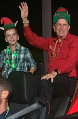 """Benjamin Peterson with Naples Mayor Bill Barnett in the annual Christmas parade. Benjamin earned the seat of honor with his essay, """"How Naples Stole the Grinch."""""""
