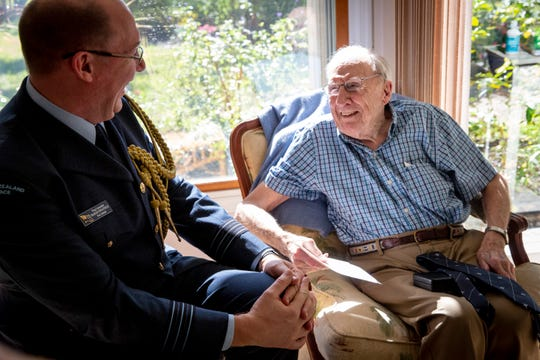 Thomas Horton, right, who served in the Royal New Zealand Air Force in WWII, receives a Defence Service Medal from Wing Commander Graham Streatfield, left, at Horton's home in Naples on Monday, Dec. 23, 2019.