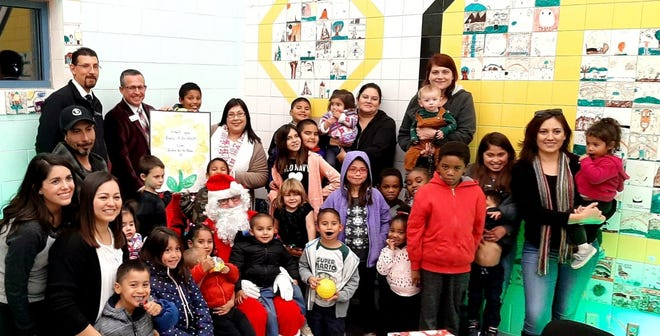 Bank of the West banker Michael Zamora, Bank of the West Vice President Osvaldo Luna, Jardín de los Niños Executive Director Michelle Adames and Jardín staff and children spend time with Santa.