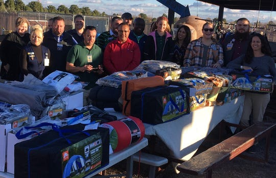 Pictured in this photo are many of the store managers from 11 southern New Mexico stores and their regional manager, Tim Walsh. Each of the stores in the region brought donations of tents and tarps for the Community of Hope.