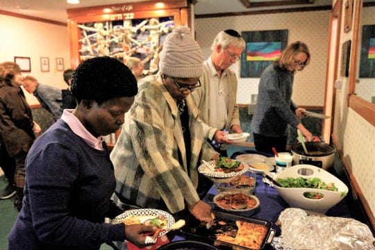 Gertrude Dandize, left, and Nomsa Nocande, right, help themselves to traditional Hanukkah foods like latkes, Sunday, Dec. 22, 2019, on the first night of the Jewish celebration of Hanukkah at Congregation Har Shalom in Durango, Colorado.
