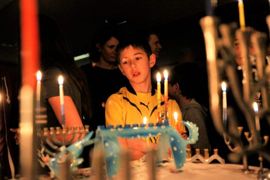 Judah Azulai participates in the lighting of candelabras called menorahs, Sunday, Dec. 22, 2019, on the first night of the Jewish celebration of Hanukkah at Congregation Har Shalom in Durango, Colorado.