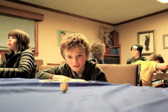 Lukas Bayer, 11, plays with a dreidel, a traditional Jewish four-sided spinning top game, Sunday, Dec. 22, 2019, on the first night of the Jewish celebration of Hanukkah at Congregation Har Shalom in Durango, Colorado.