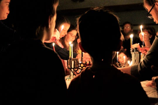 Members of Congregation Har Shalom light candelabras called menorahs, Sunday, Dec. 22, 2019,  on the first night of the Jewish celebration of Hanukkah at Congregation Har Shalom in Durango, Colorado.
