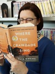 Baldwin Public Library employee Rebekah Craft checks out Delia Owens' Where the Crawdads Sing.