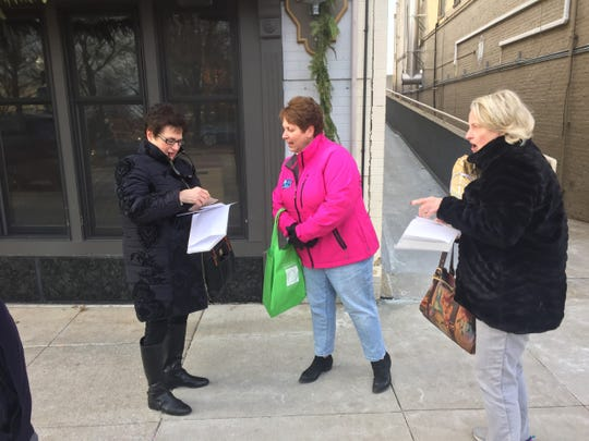 Mary Ann Sincock (left) and Diane Tracey (right) react as they look through the gift cards they received.