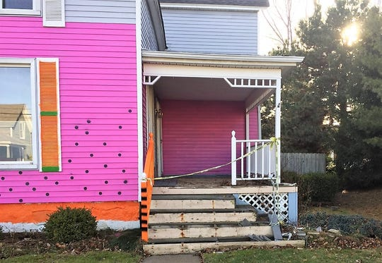 The front porch of Plymouth's pink house is cordoned off with yellow caution tape.
