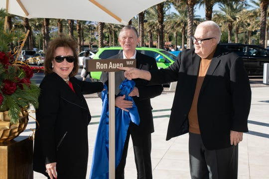 Sherrie Auen unveils a replica sign of Ron Auen Way, in honor of her late husband, at Eisenhower Health. G. Aubrey Serfling and Christopher McGuire spoke at the dedication ceremony.