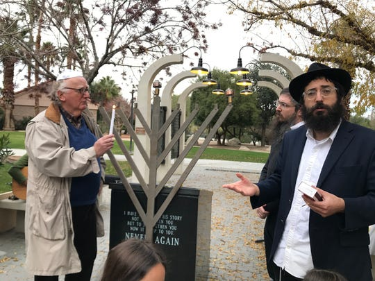 Steven Geiger, left, lights the first candle on the menorah while Rabbi Boz Werdiger speaks at a celebration marking the start of Hanukkah on Sunday, December 22, 2019, at the Holocaust Memorial at Palm Desert's Civic Center Park.