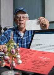 Mike Esmond shows some of the letters and emails recognizing his generosity that he has received from around the country and the world at his home in Gulf Breeze on Monday, Dec. 23, 2019. Esmond has garnered worldwide attention for paying the utility bills for 36 area residents to keep their power on during the Christmas season.